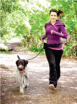 Woman running on trail with dog.